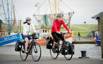 Cycling along traditional fisher-boats at the habour of Dorum-Neufeld