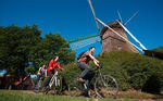 Cyclists in front of the windmill Mersmühle in Haren